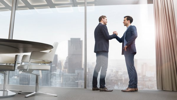 Two managers shaking hands in a modern office