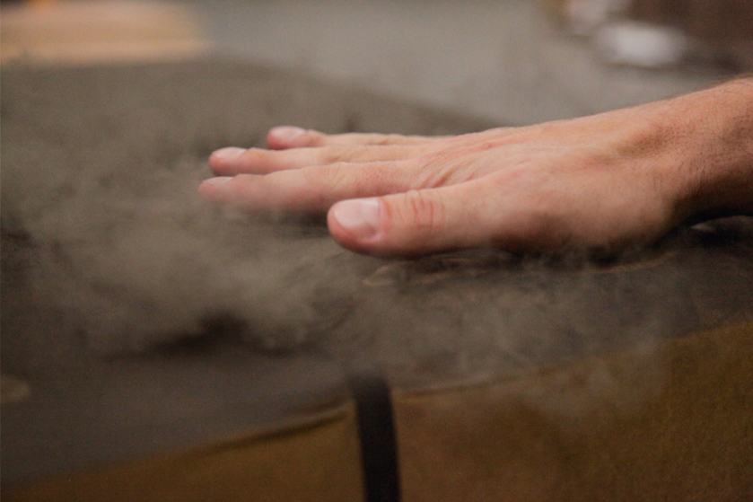 Hand touching a dirty parcel and whirling up dust