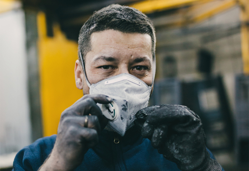 Dirty manufacturing worker holding his face mask with dirty hands
