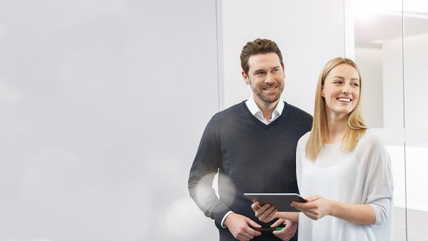 Two employees smiling and holding a tablet